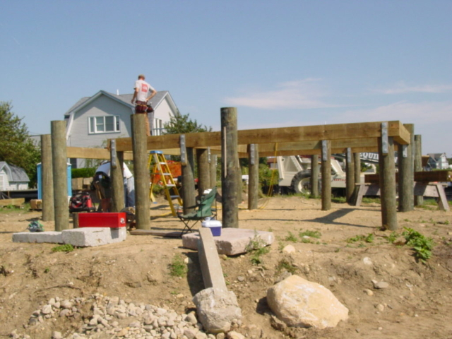 Large pressure treated timbers attached to pilings